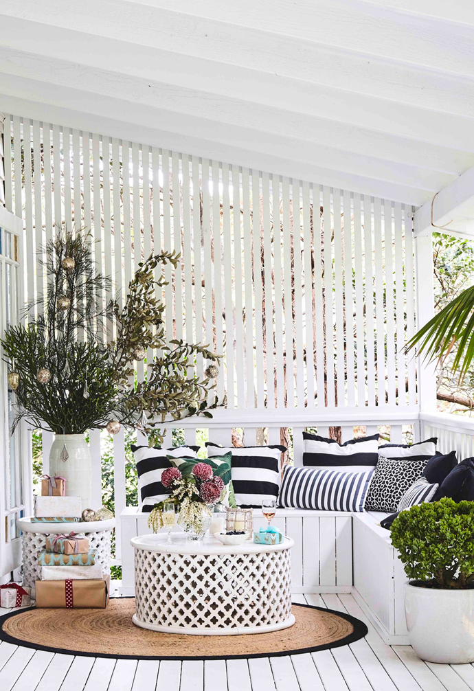"""When Sally and Ben first saw their home, they quickly fell in love with the front verandah, particularly the nook at the end, encased in greenery. """"We call it the G&T corner!"""" says Sally. """"When we moved in, it was dingy with no appeal, so I had the bench seat and screen built, and now everyone gathers here."""""""