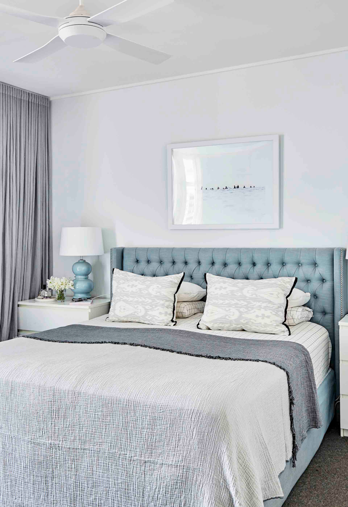 """""""I think bedrooms should be really simple and calming, with as little clutter as possible,"""" says Sally of the main bedroom, which features curtains in dusty grey and a soft blue bedhead from Mayvn Interiors."""