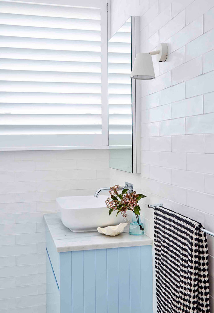 """""""I spend my life designing bathrooms, so I wanted to do something at least a little brave for my own,"""" says Sally, who chose a baby blue – Dulux Oriental Bay – for the bathroom vanity, a colour she loved so much, she had to repeat it for the front door of their property. Aside from this appealing splash of colour, Sally kept the palette very simple in the bathroom, with marble tiles across the floor and handmade subways from Tiles By Kate on the walls. """"The space is seriously tiny, so I let the materials do the talking,"""" she explains."""