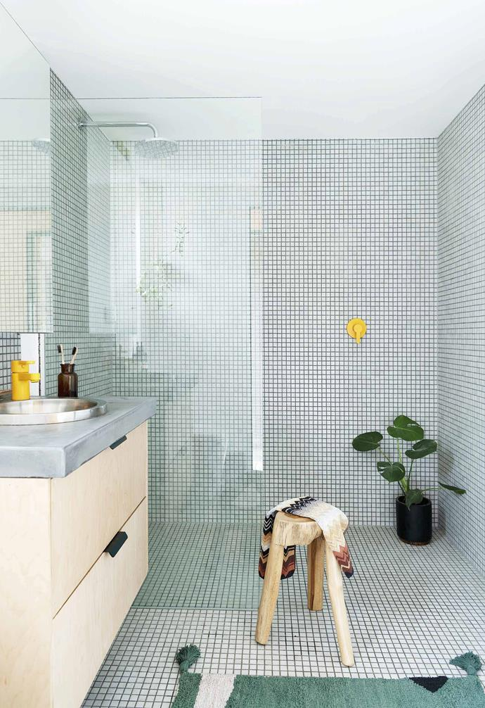 This compact eco-friendly home in Perth is full of clever design ideas. In the bathroom, green mosaic tiles are paired with a timber and concrete vanity, while bright yellow tapware adds a playful accent.