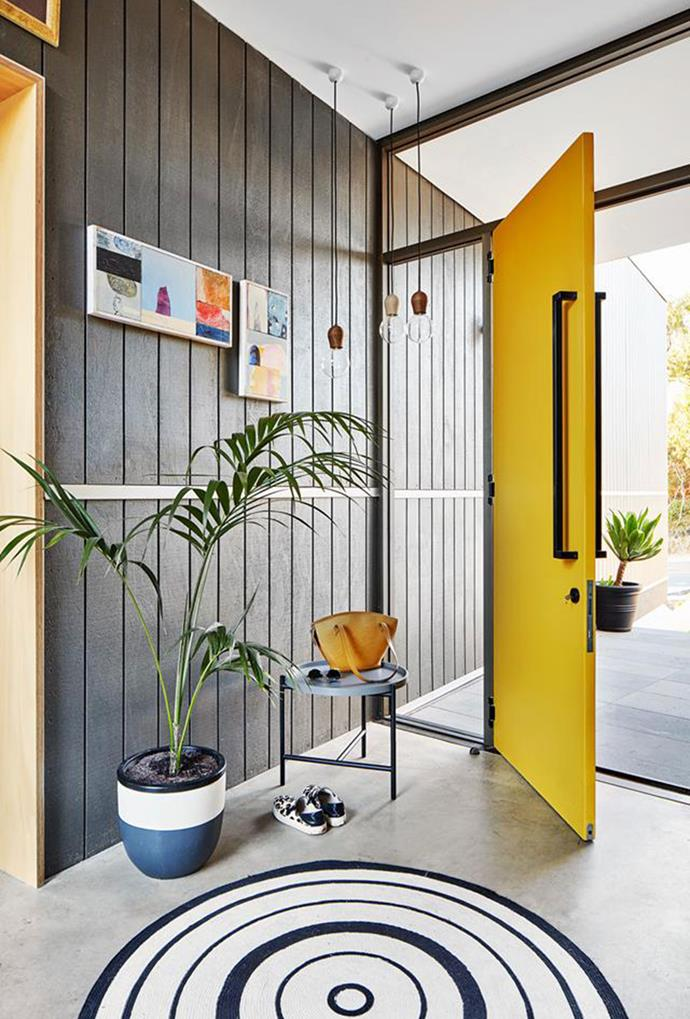 Gen-Z Yellow is not only featured on the front door of this home, but throughout the main bedroom and interior, adding impact to an otherwise neutral palette. The sunny front door adds a bright touch when paired with the concrete flooring and panelled walls.