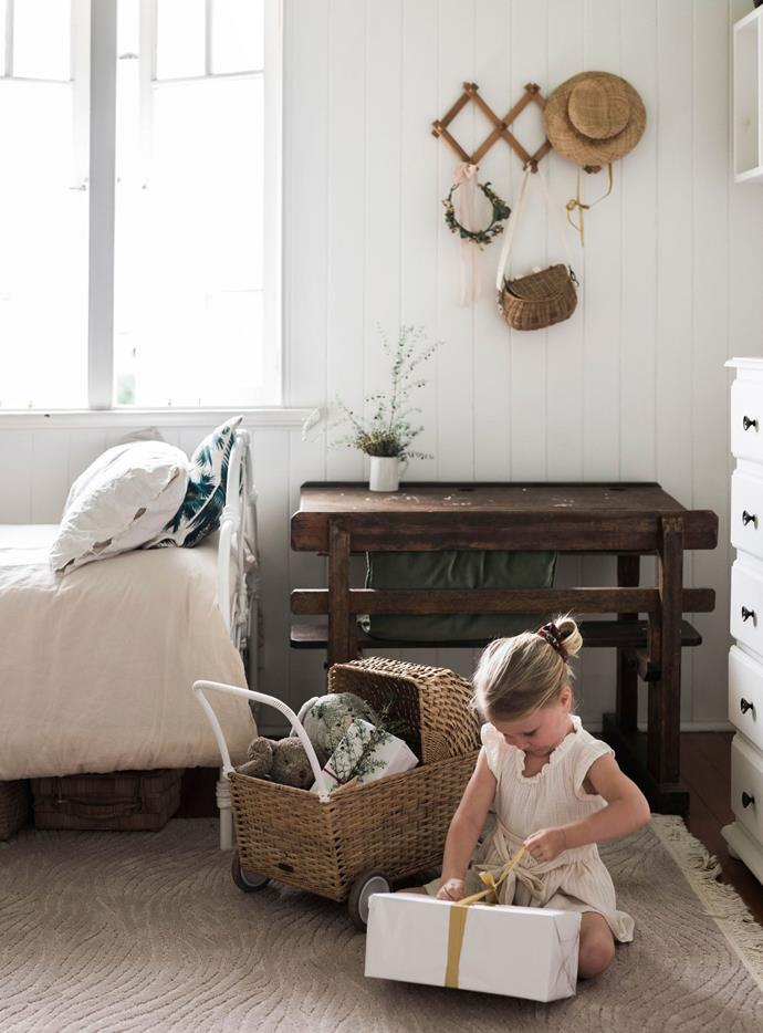 Scarlett plays in her room with her Olli Ella pram. On the wall is a vintage expandable hook rack that belonged to Hayley as a child.