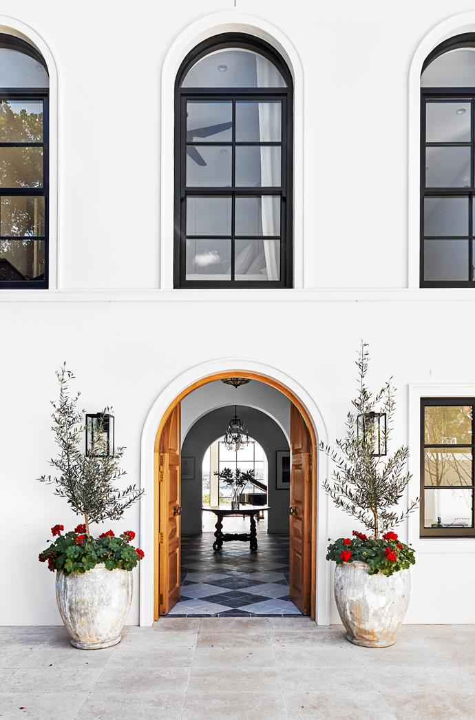 Flanking the arched front doors, a pair of original Ross Street pots hold scarlet geraniums and olive trees. Travertine pavers from Aeria Country Floors.