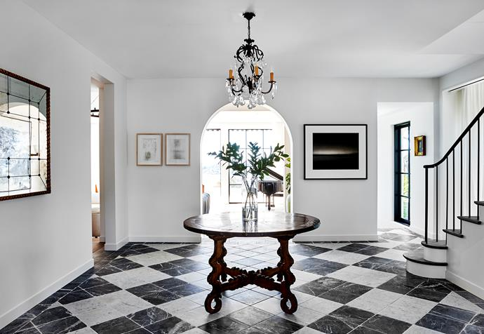 A vintage Belgian chandelier hangs in the entry over a Spanish Carlos II round table with churrigueresque base in European oak. Pair of artworks by Ana Pollak. Black and white photograph by Laurence Aberhart. Italian marble floor tiles from Aeria Country Floors.