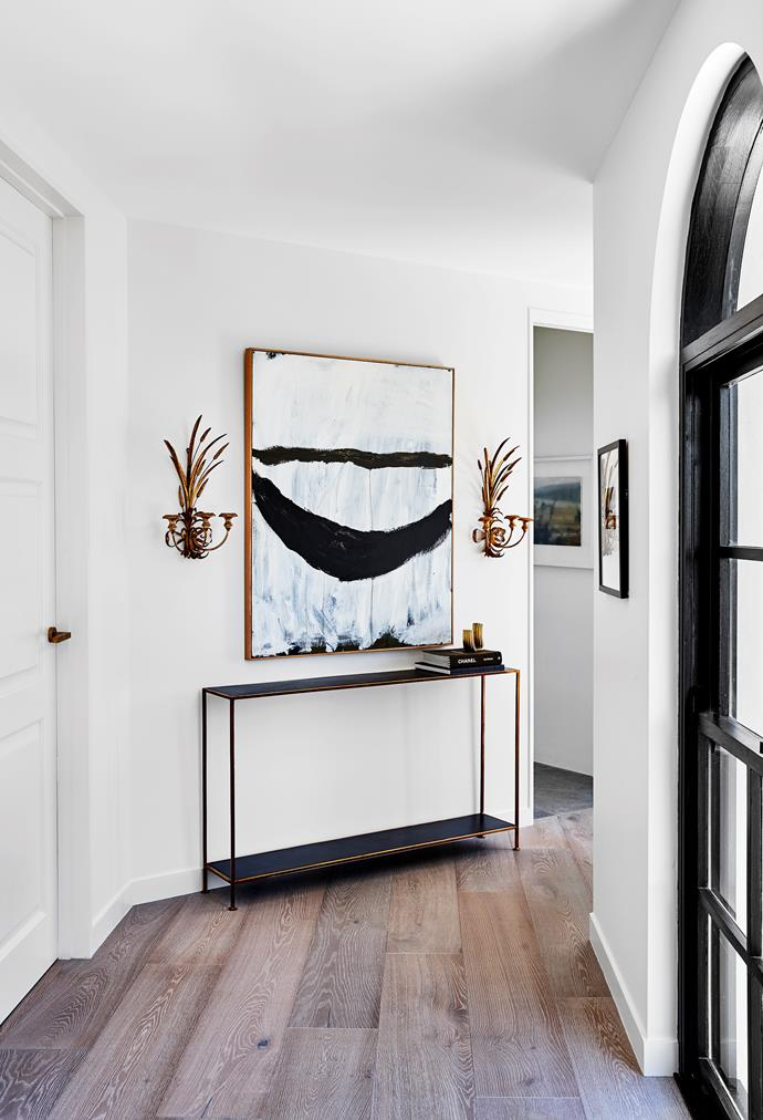 Above an antique metal console with brass trim is a pair of Hollywood Regency wheat brass sconces and an artwork by Newcastle-based artist Lottie Consalvo.