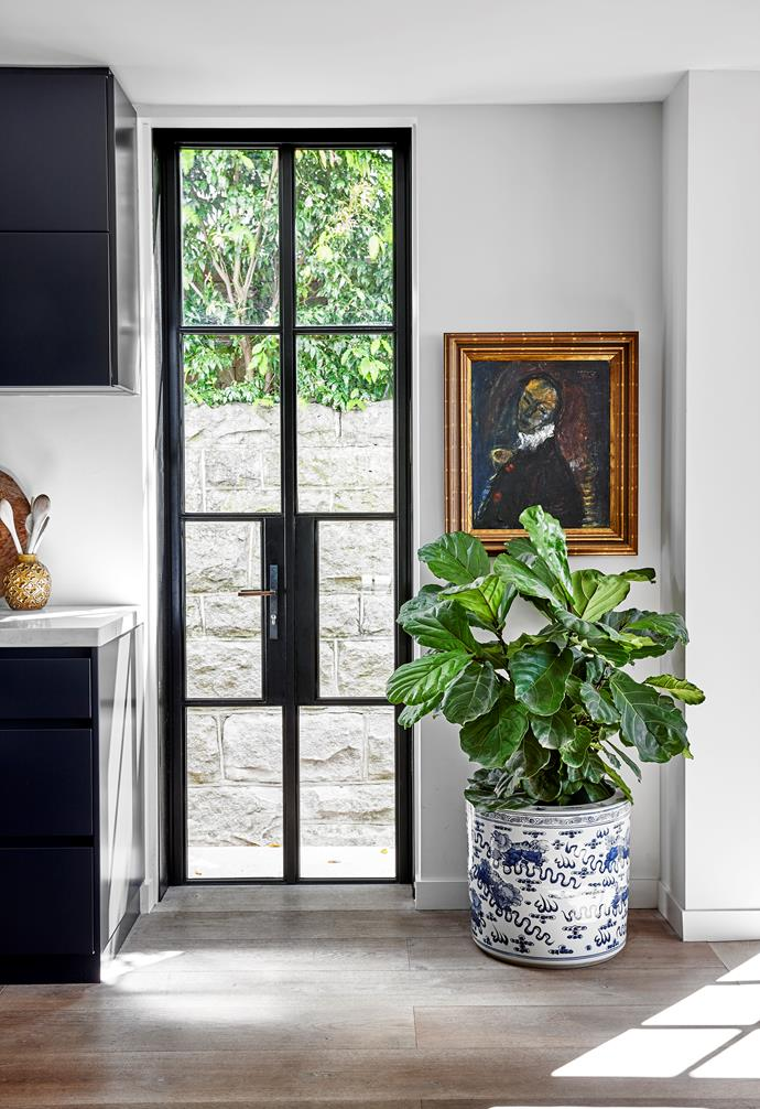 An Alf Lindberg artwork hangs in the kitchen next to steel-framed black doors from Skyrange Windows.