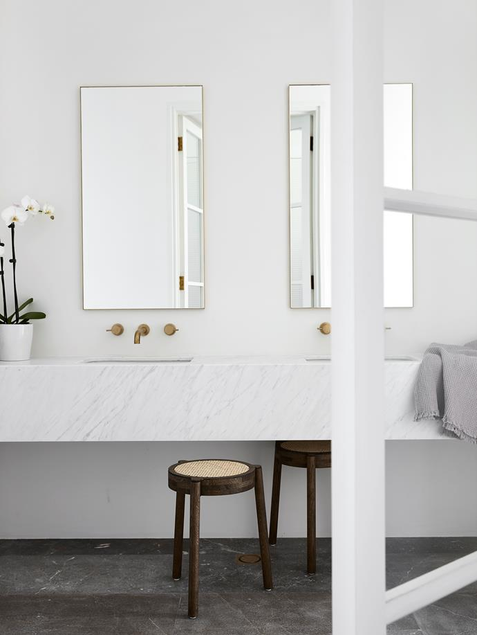 The bathroom features a benchtop in Carrara marble from SNB Stone. Brass tapware by Brodware. Custom aged brass mirrors from All Aspects Joinery. Smoked limestone floor tiles from Aeria Country Floors.