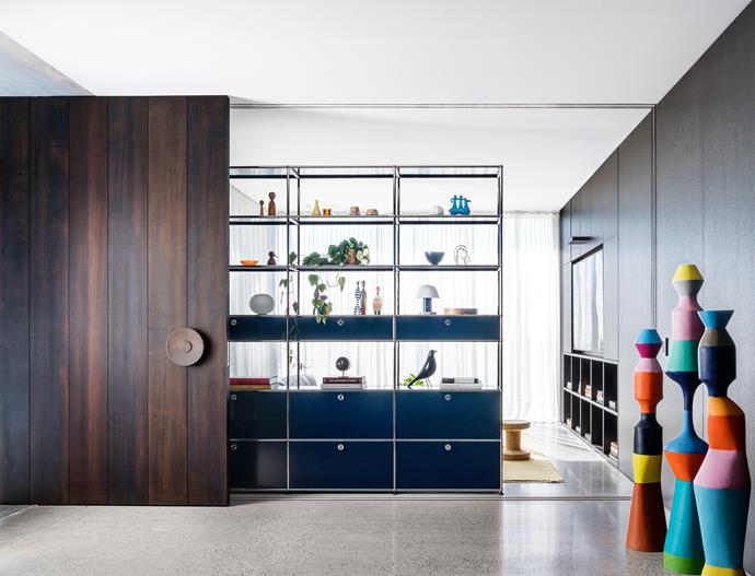 The heavy front door is in stained cedar with a custom brass handle by Tobias Partners. USM shelving unit from Anibou holds Vitra 'Eames House Bird', 'Wooden Dolls' and 'Desk Clock' from Living Edge. Totem artworks by Stephen Ormandy from Olsen Gallery. Smoked oak joinery.