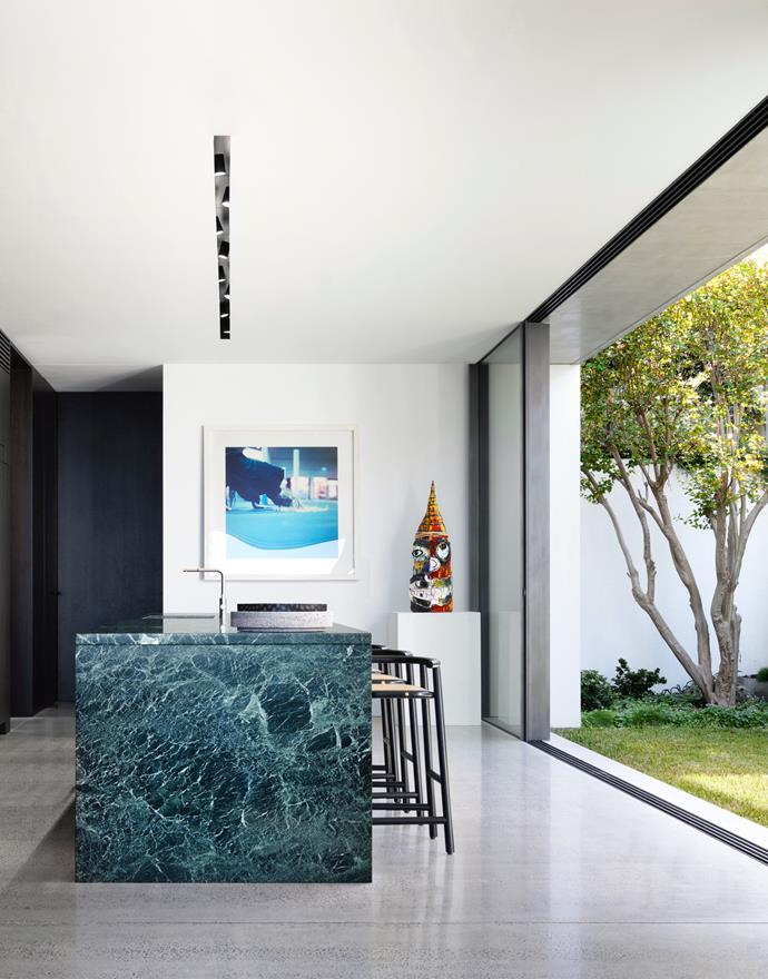 The kitchen opens to the side garden allowing a connection with the outdoors and admitting abundant natural light. Smoked oak joinery. Benchtop in Verde Tinos marble from Euro Marble. Gebrüder Thonet Vienna 'Single Curve' stools from Space. When Objects Work 'HH' bowl from Hub. Artwork is Woolloomooloo Nights by Shaun Gladwell. Sculpture is Figure with Red Crown by Ramesh Mario Nithiyendran. Polished concrete floor. Opposite page