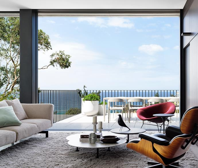 The living area enjoys panoramic views over the beach. Knoll 'Avio' sofa and 'Diamond' armchair, 'Saarinen Tulip' side table, 'Grasshopper' coffee tables, and Minotti 'Wisp' rug and bowl, all from De De Ce. Herman Miller 'Eames' lounge chair from Living Edge. Digital Organic Mineral V11 table sculpture in white marble by Stephen Ormandy from Olsen Gallery. Tribù 'Illum' outdoor setting from Cosh Living.