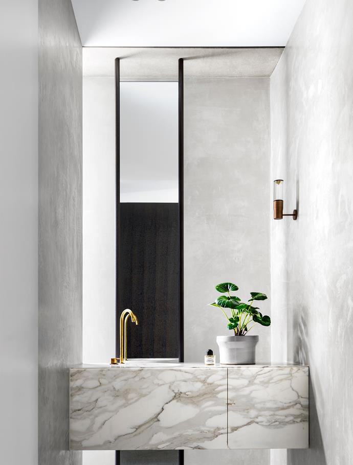 The powder room has a Calacatta marble vanity from Euro Marble with Vola tapware. Custom mirror designed by Tobias Partners. Viabizzuno 'Royal Parete' wall light.