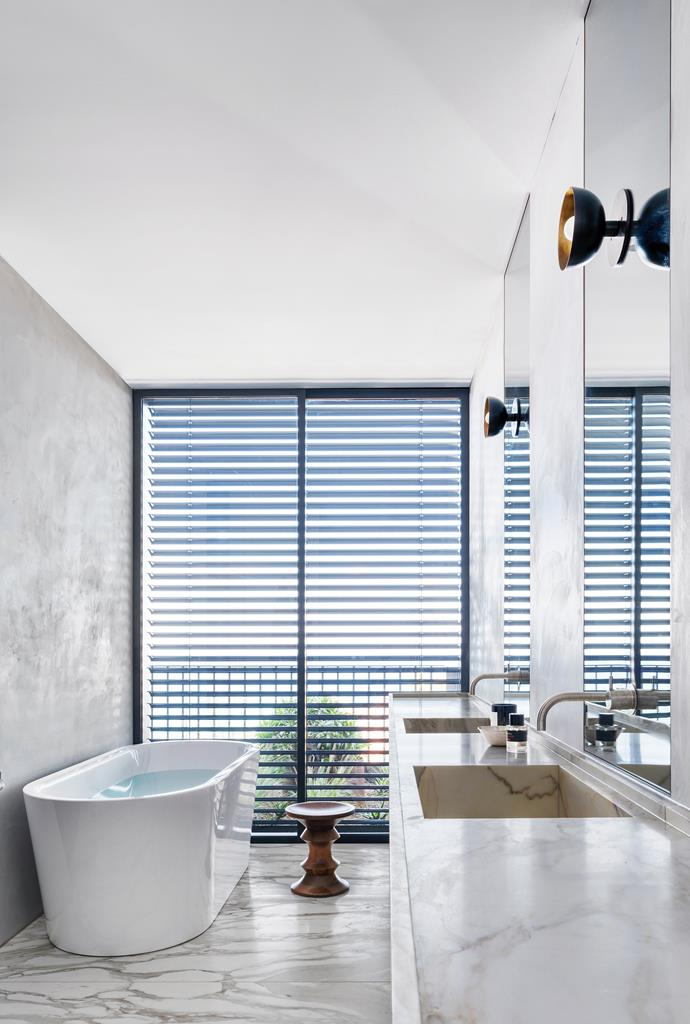 The ensuite has a Kaldewei bath from Sydney Tap and Bathroomware. Vanity and floor tiles in Calacatta marble from Euro Marble. Apparatus 'Trapeze' wall lights from Criteria. Herman Miller 'Eames Walnut' stool from Living Edge.