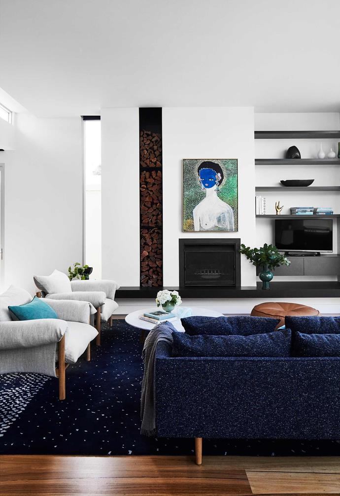 """**Living room** The floor-to-ceiling column of firewood is a feature in itself. The fireplace hearth is Zimbabwe Black leather-finish granite. Nook sofa in Fleck Neptune and Wilfred chair in Seaspray linen, Iko coffee table and Alby leather floor cushion, all [Jardan](https://www.jardan.com.au/