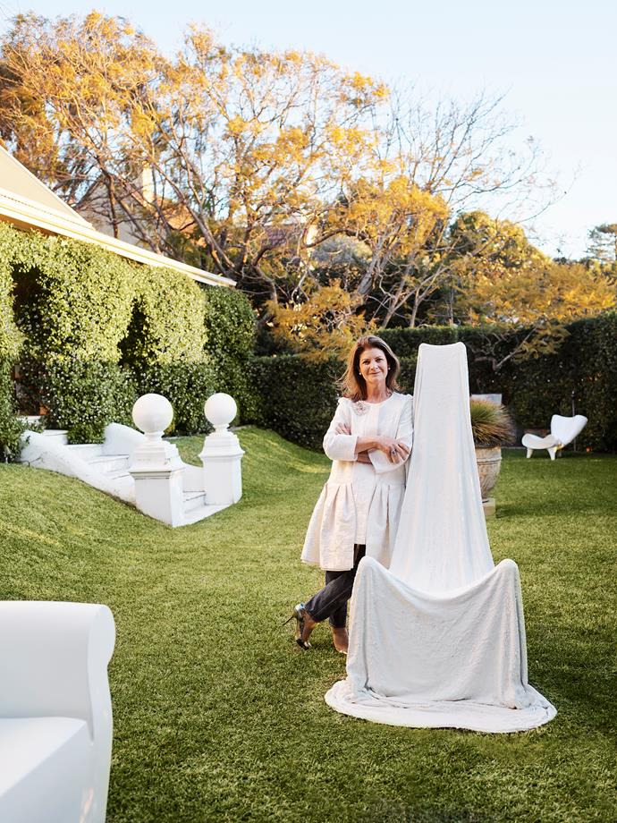 In the garden of her home in Sydney's eastern suburbs, Sally Dan-Cuthbert leans on Layman's Throne, a work in cement and plasticised terry towelling by Andre Bahremand, who is represented by her gallery. One of a pair of white Marc Newson 'Orgone' chairs can be seen in the background.