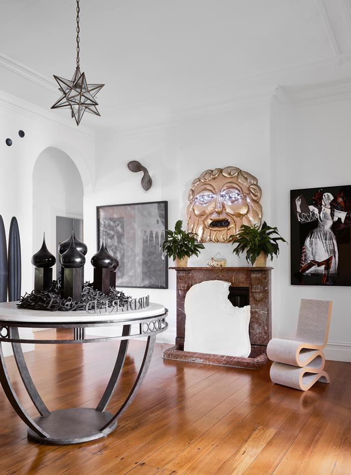A dazzling gold mask by Tarryn Gill, titled Belly of the Beast, and Frank Gehry's iconic cardboard 'Wiggle' chair greet visitors in the entrance hall of the home. On the mantel is Pond Body III, a sculptural work by Honey Long and Prue Stent. To the right is Sally Smart's painting and collage, *Pedagogical Dance (Hand Movement)*, while to the left is a drawing by Brendan van Hek with Bronwyn Oliver's Pair copper wall sculpture installed above it. A custom bronzed iron table holds Emily Floyd's *I Murdered* sculpture. Artwork on hearth, *All That is Solid Melts* by Sherna Teperson.