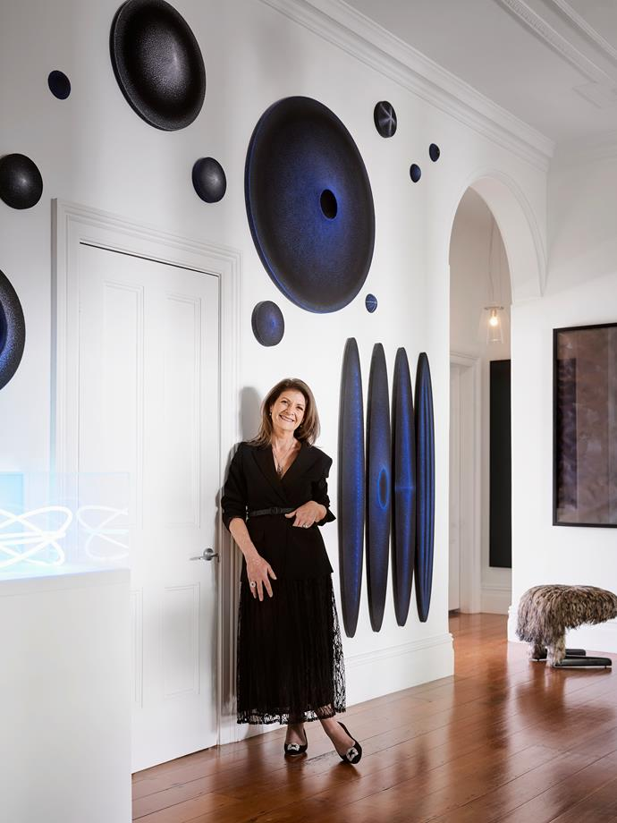 Sally in the entrance hall in front of gallery artist Marion Borgelt's extensive wall installation, *Nothing is Invisible*. The neon work on the plinth is *Brilliant Standard Ice* by Vanila Netto. Gallery artist David Tate's At Rest stool is upholstered in emu feathers on cotton.