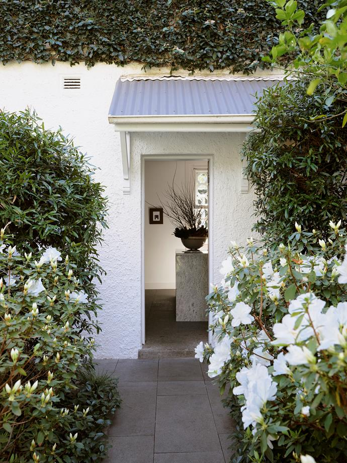 The house is surrounded by gardens on each side and different flowers bloom throughout the year.