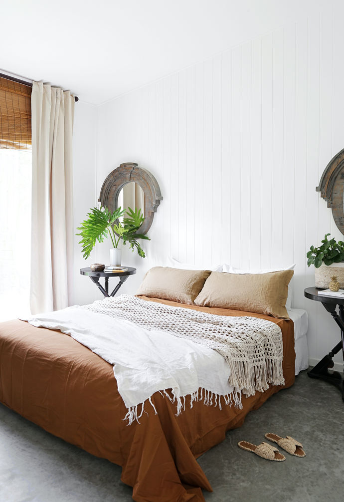 VJ walls are matched with rustic mirrors Kim and Ian  brought with them from the US to give a subtle textural backdrop. On the bed, a linen quilt cover layered with a crochet throw from Harper St is relaxed yet chic, and plants and foliage from the garden add a lush touch atop bedside tables bought from a jazz club in Brisbane.