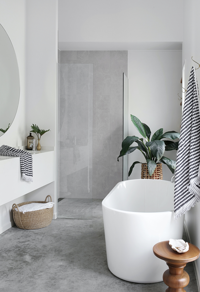 """Countless Pinterest images helped inspire the sleek ensuite in soothing grey and white. """"I wanted a seamless look and feel, which the concrete floor achieves by flowing through to the shower area,"""" says Kim, who used 'Bora Ice White' polished 600mm x 600mm tiles from Cheap Tiles Online to create the illusion of concrete continuing up the walls."""