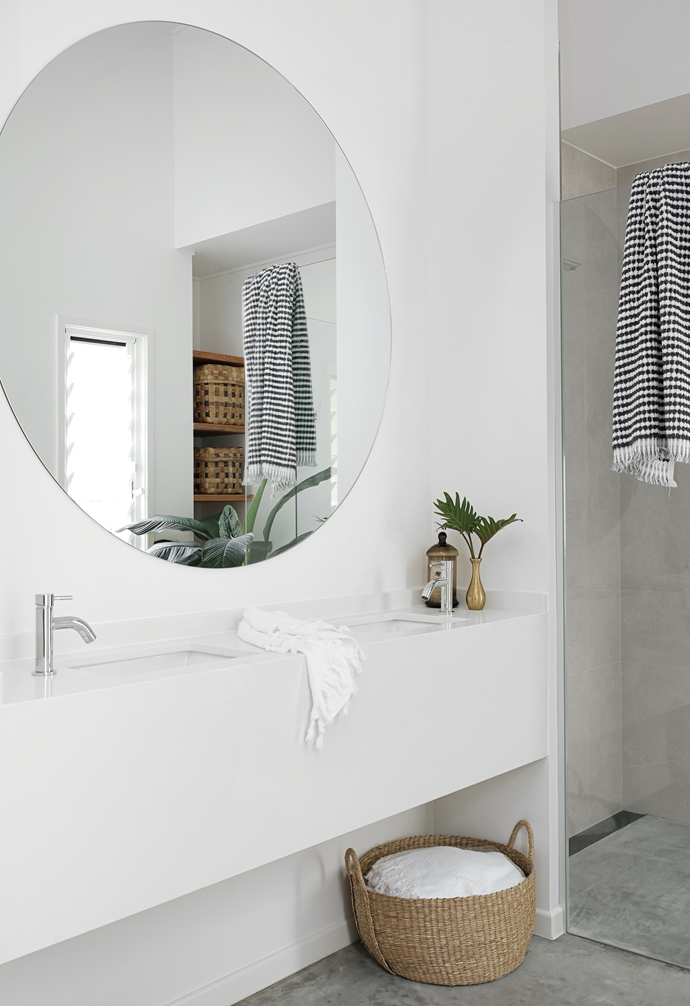 The vanity features the same Smartstone used in the kitchen and is paired with Mondella tapware from Bunnings. The organic curves of a round custom mirror are echoed in a Caroma 'Aura' freestanding bath from Reece and, with a stool from Gumtree, bring a sense of softness.