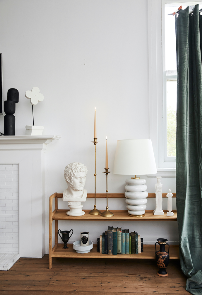 Flower sculpture (on fireplace), $450, Den Holm. SCP 'Agnes' long bookshelves in Oak, $3165, Hub Furniture. On top shelf, from left: Bust, stylist's own. Vintage brass candle holders, $645/part of a set of 3, Becker Minty. Kelly Wearstler 'Phoebe' stacked table lamp in Antique White with linen shade, $1795, Becker Minty. 'Caryatid Female Figure' sculpture, $290, and 'Iniohos Statue' sculpture, $89, both Mercer & Lewis. On bottom shelf: 'Kantharos' vessel, $425, Mercer & Lewis. Giobagnara for Becker Minty 'Agora' round suede bowl in Sky, $545, Becker Minty. Officine Universelle Buly candle in Alexandrie, $231, Mecca. 'Palazzo' bookends in Foresta, Travertine and Nero, $770, Greg Natale. Vintage books, stylist's own. 'Amphora' pot (on ground), $425, Mercer & Lewis. 'Delhi' velvet curtain in Celadon, $289, Montmartre.