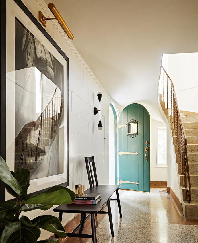A turquoise front door with gleaming brass hinges and handles opens to the entry where there is a portrait of Christy Turlington photographed by James. The couple restored the original terrazzo floor.
