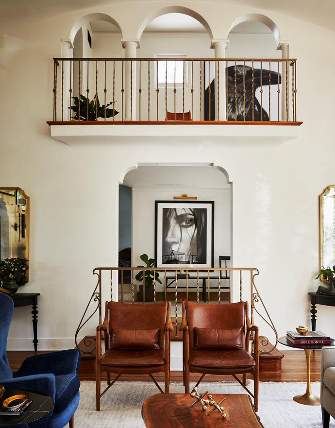 The leather chairs are from Industry West and the walnut coffee table was designed by James. The 5.5-metre high living room has a small mezzanine balcony. James shot both the monochrome photographs.