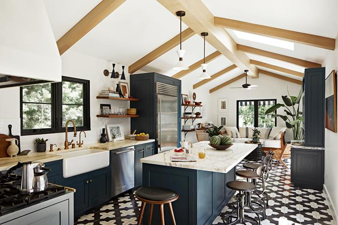 The kitchen was designed with a pitched roof and white oak beams which give it a light, airy feeling. The cabinets are painted in Farrow & Ball 'Hague Blue' 