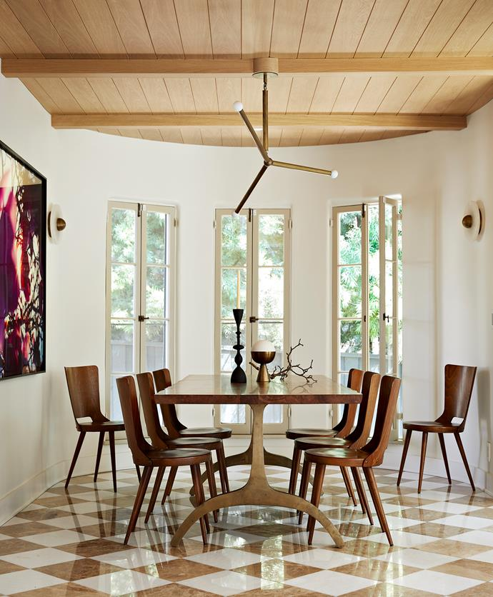 The vintage French bistro dining chairs were found at 1stdibs. The couple added the white-oak timbered ceiling in the dining room and re-laid the floor in Italian marble tiles.