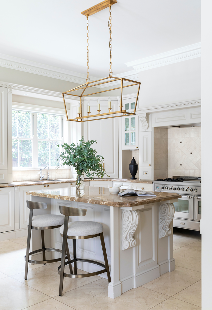 """With a splashback of lustrous Crema Marfil tiles from Stone Design and Liban beige marble benchtops from Gitani Stone, the kitchen matches practicality with panache. """"It feels quite luxe, but it's so functional,"""" says Joumana. """"There's not a stain on the marble, and I cook maybe four nights a week."""" Midweek meals takeplace at the island, where Boyd Blue 'Frankie' bar stools and a 'Darlana' linear lantern from Circa Lighting deliver a dramatic dose of contemporary style. The black benchtop urn is from Coco Republic."""