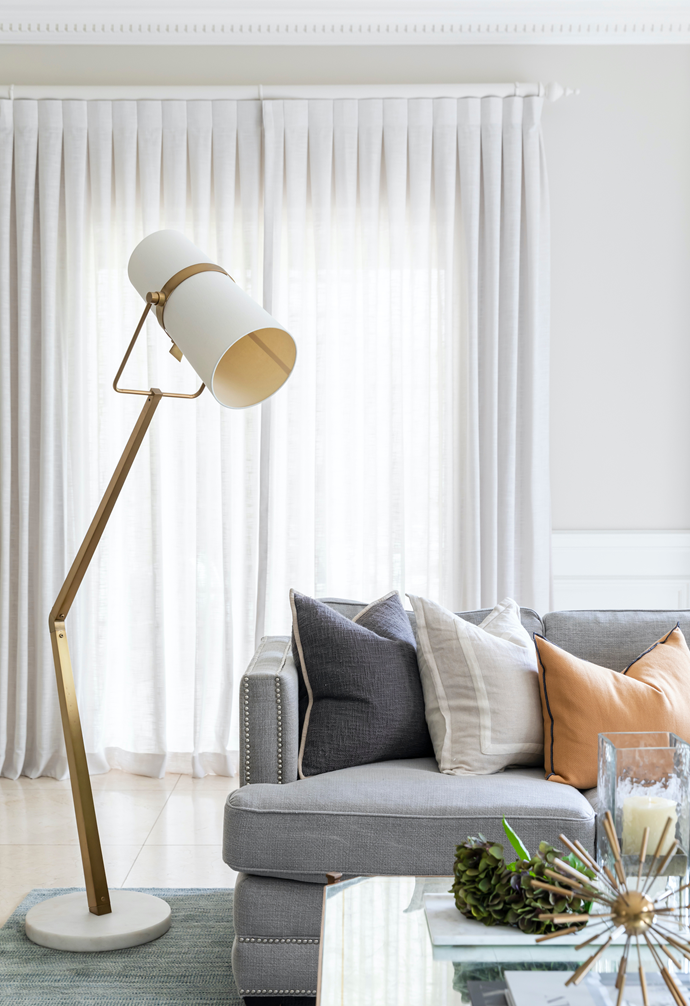 The Arteriors 'Juniper' floor lamp in Antique Brass from Boyd Blue makes a statement in the family room.