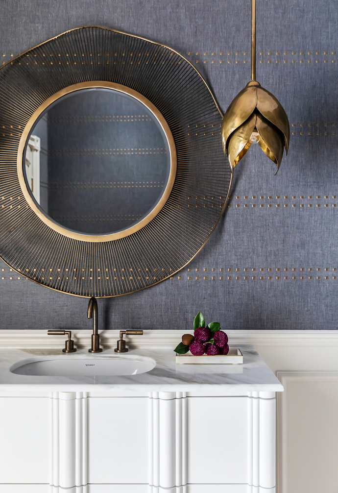Style takes a dramatic turn in the stunning powder room that features a marble-topped vanity and a stunningly circular Arteriors 'Olympia' antique brass wire mirror from Boyd Blue. The Arteriors 'Edith' pendant, also from Boyd Blue is a stand-out match in brass.