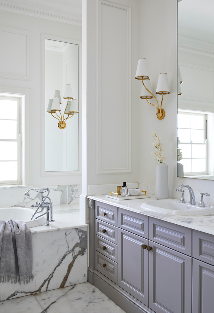 """Boasting a cooler colour palette than the rest of the home, Joumana and Daniel's ensuite is a style-filled sanctuary. """"We wanted it to feel fresh and light,"""" says Joumana. Lashings of Calacatta Oro marble from Gitani Stone line the floor, bath and custom vanity, which Joumana recently topped with custom mirrors to echo the dimensions of the adjacent wall panelling."""