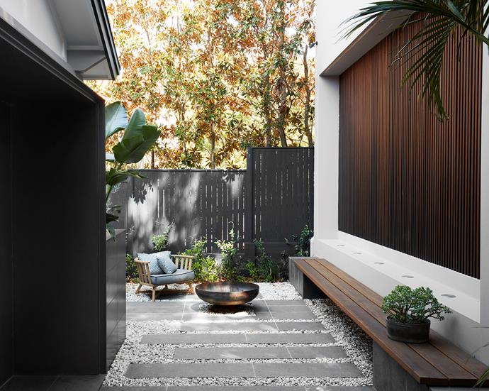 The battened screen on the garage doubles as a decorative feature of the courtyard. Gervasoni 'InOut' chair, Anibou. Sesame Grey stone pavers, Sam the Paving Man. The bench seat is blackbutt stained in Sikkens Cetol black japan.