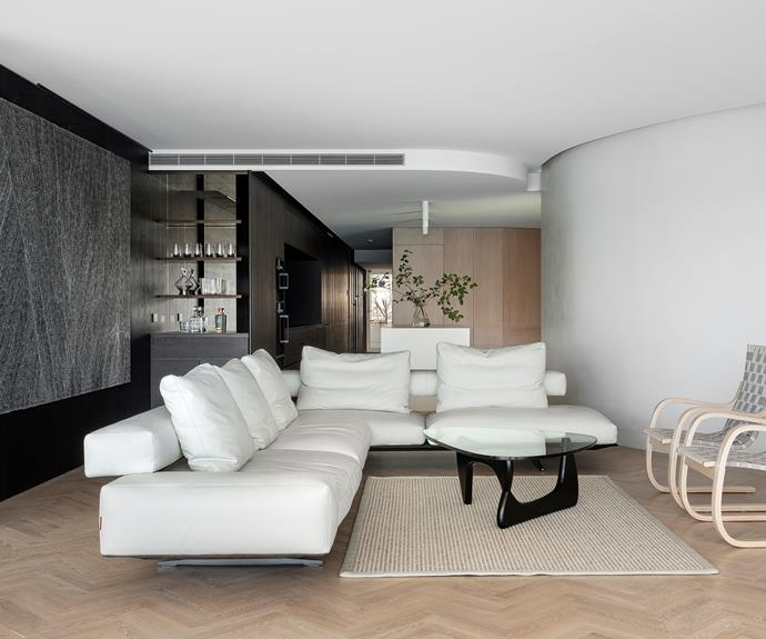 The Dorothy Napangardi artwork set the tone for the dark core that extends to the entry lobby. All other finishes are in a light, high key. Flexform 'Wing' sofa from Fanuli. Artek '406' armchairs from Anibou. Vitra 'Noguchi' coffee table from Living Edge on a rug from Natural Floorcovering Centres.