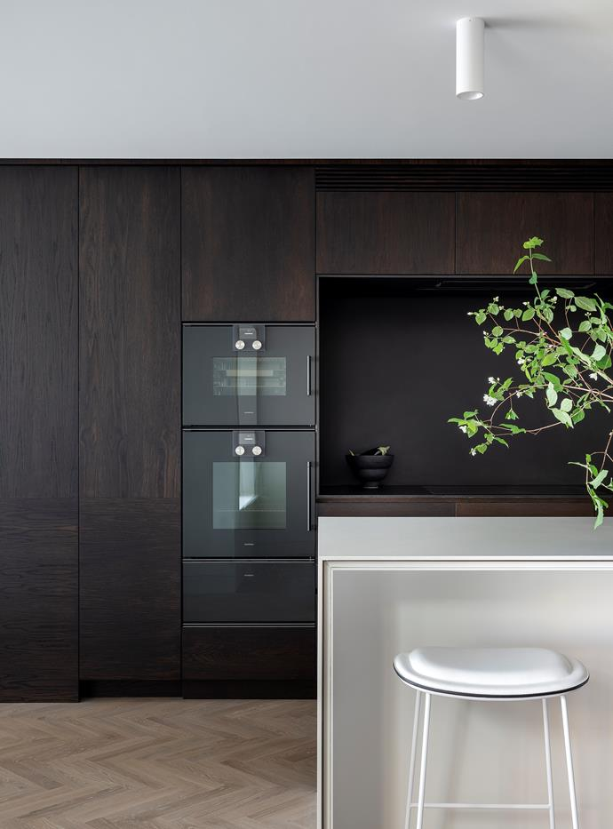 Joinery in Smoked Oak veneer by Briggs Veneers contains all services, including kitchen fixtures. Ovens from Gaggenau. Benchtop, splashback and surround in Maximum 'Pepper' porcelain sheets from Artedomus. Emily Belle Ellis bowl from The DEA Store. 'Hi Pad' stool by Jasper Morrison from Cult.