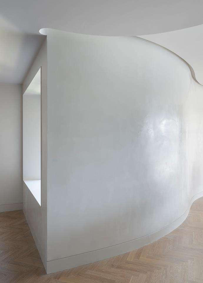 The curved wall and counter-curved ceiling read sculpturally in the space. Window reveals in Maximum 'Saturn' porcelain sheets from Artedomus.