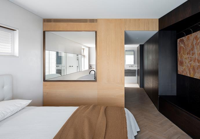 The dark core terminates at the master bedroom. Brass and pale oak frame the internal ensuite window which is privacy controlled at a switch. 'Serenade' bed from King. Society Limonta bed linen and throw from Ondene. Artwork by Sarita King from Kate Owen Gallery. Walls finished in Smoked Oak and American Oak veneers from Briggs Veneers.