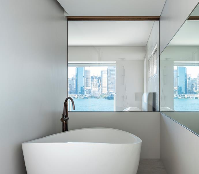 In the ensuite views are captured from the shower and the bath as well as the mirror from Viridian Glass. Appaiser 'Oman' stone bath from Just Bathroomware. Astra Walker 'Icon' floor-mounted mixer in Aged Brass from Just Bathroomware. Walls and floors in porcelain sheets from Artedomus.