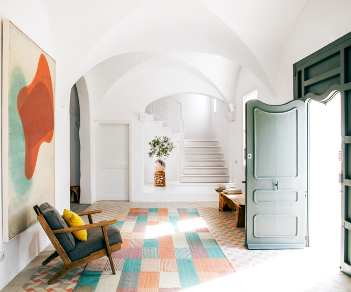 Upon entry, guests are greeted by whitewashed interiors that give way to a spectrum of colours. A painting by Ezra Siegel inspired the palette of the custom Nanimarquina checked rug and muted green door.