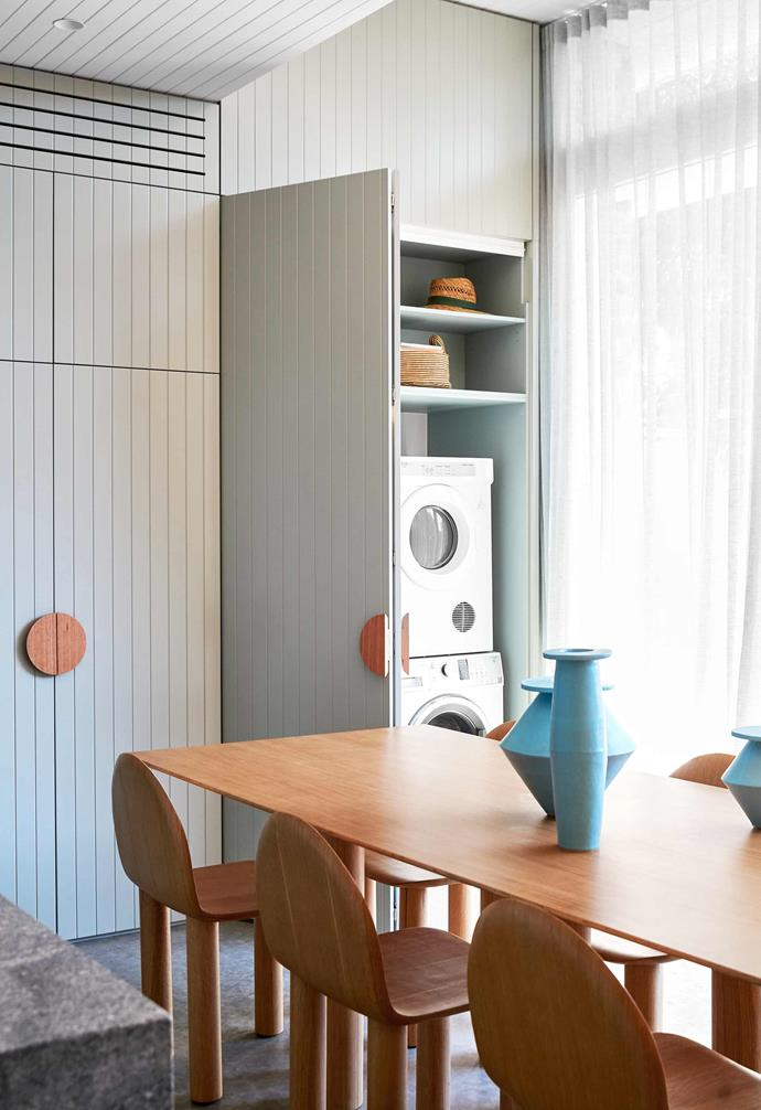 """**Laundry** Caitlin's integrated laundry has [Fisher & Paykel](https://www.fisherpaykel.com/au/ target=""""_blank"""" rel=""""nofollow"""") appliances stacked next to a small sink with a hanging rail above (both [ABI Interiors](https://www.abiinteriors.com.au/ target=""""_blank"""" rel=""""nofollow"""")). The door handles are flat, half-moon timber handles from [Auburn Woodturning](https://www.auburnwoodturning.com.au/ target=""""_blank"""" rel=""""nofollow""""). """"I specified a bifold mechanism to the laundry doors, which gives us easy, unobstructed access to the space,"""" says Caitlin."""