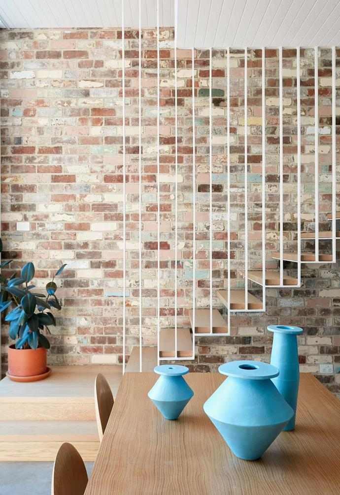 """**Staircase** Exposed brick in the kitchen and stairwell adds a depth of colour to the interiors, which is amplified by the use of cantilevered solid American oak steps. """"Finishing with a thin, white painted-steel balustrade makes the staircase seem light and airy,"""" says Caitlin."""