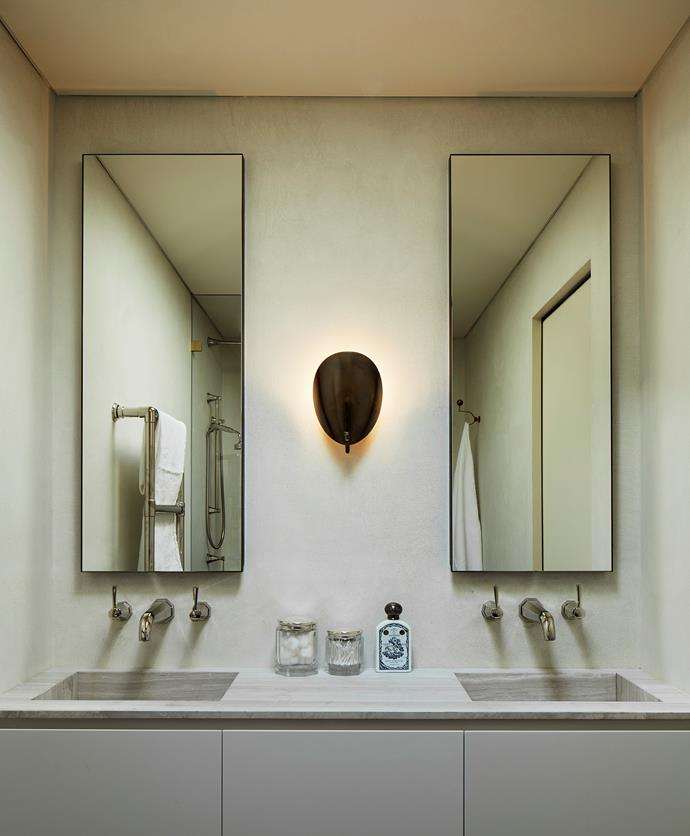 The ensuite has a wall sconce from 1stdibs. Tapware from The English Tapware Company. Walls in microcement finish.