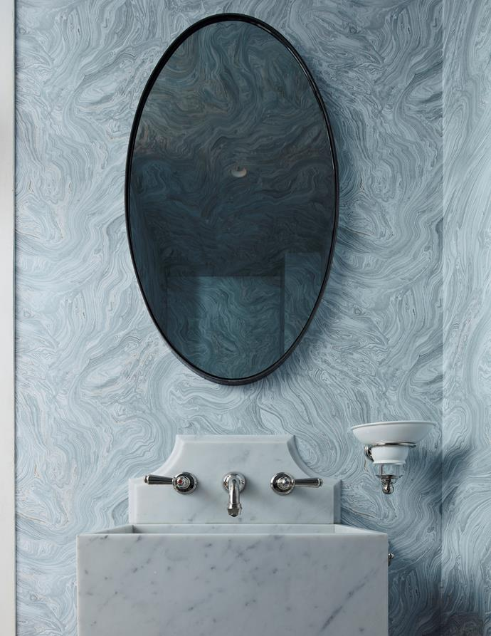 The powder room has Thibaut 'Venus' wallpaper in Sky from Boyac, a custom Carrara marble basin and oval mirror.