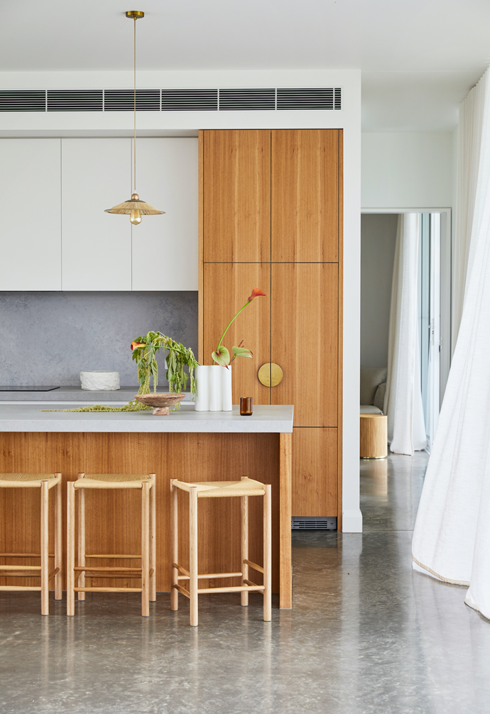 """The couple went for a mix of textured materials including blackbutt cabinetry, brushed brass door handles from Lo & Co, brass and rattan pendants by Tigmi Trading and Caesarstone 'Airy' concrete for the benchtops and splashback. """"There's lots of storage to maintain our minimalistic aesthetic and hide the mess,"""" Sally says."""