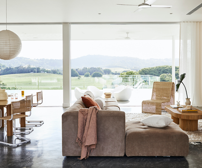 """Sally has filled her home with a mix of second-hand and new pieces, including a Tigmi Trading rug, a modular sofa from HK Living and a Sarah Ellison coffee table. """"Sarah's collection seems to match my style perfectly."""" The curvy chair is from Byron Bay Hanging Chairs. The throw, white square cushion and ceramic objects are all from Nikau Store. The bolster is from Clo Studios."""