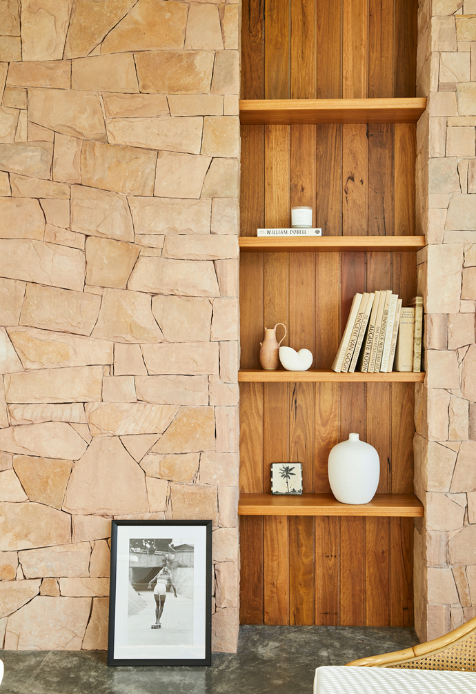 """A timber bookcase is built into the stone-clad wall, which """"was our nod to the mid-century architecture,"""" Sally says."""