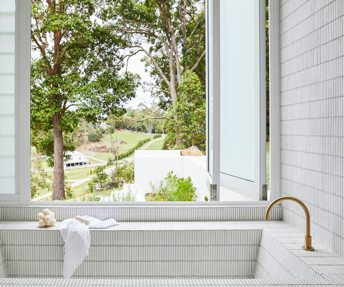A textural, neutral palette of mosaic tiles in the bathroom ties in with the rest of the home and the view from the window.