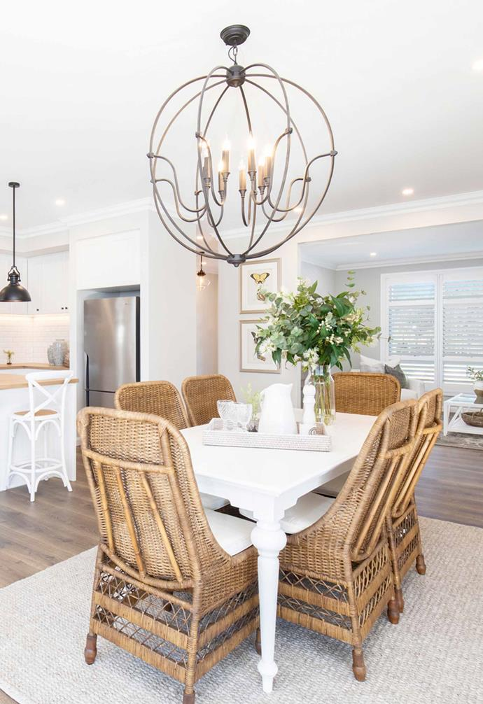 The open-plan kitchen, living and dining area all connect seamlessly to the outdoor entertaining area courtesy of sliding doors. A neutral rug was added to clearly carve out a dedicated dining zone where rattan dining chairs and a white dining table add a relaxed touch.