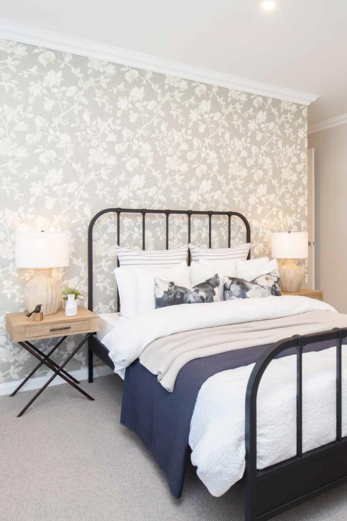 "In the [master bedroom](https://www.homestolove.com.au/modern-bedroom-ideas-18706|target=""_blank"") a country-inspired wrought iron bedframe is paired with a floral wallpaper."